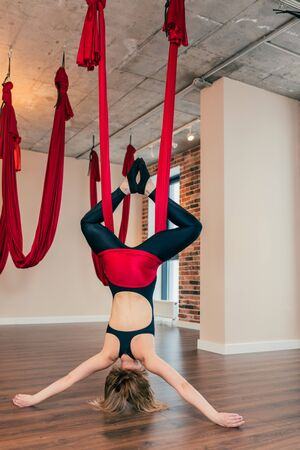 Young woman practices aerial inversion anti-gravity yoga with a hammock in a loft studio. Female gymnast performs physical exercises fly-yoga, pilates, restorative decompression flip.