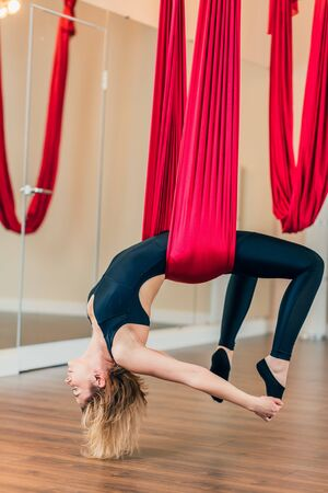 Yogi female trainee learning to relax, focusing on her body and feelings, control her breathing while training in the air on hammock in inverted body positions. Anti-gravity Yoga concept