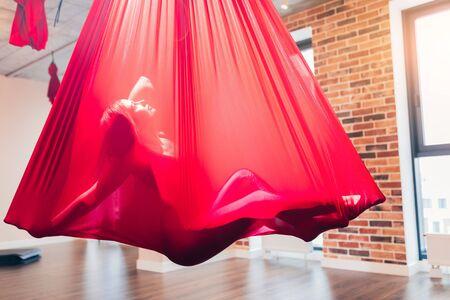 Jeune femme exécutant une danse créative utilisant un hamac rouge comme équipement de suspension pour la danse, son corps est complètement caché par un hamac rouge comme dans l'utérus