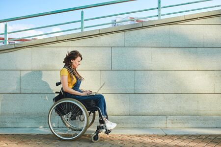 serious girl walking with wheelchair, full length side view photo. copy space.woman having a video chat, making a video call. 写真素材