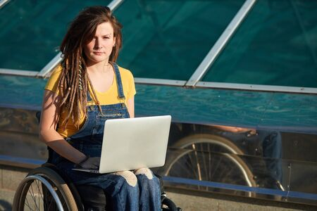 young hipster girl with laptop looking at the camera. close up portrait, blogger, copy space.girl was disabled by the accident Stockfoto