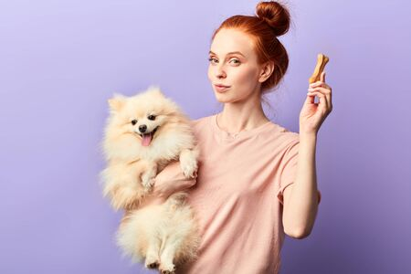 awesome attractive pet owner going to give a bone to her favourite dog. lifestyle, interest, hobby, free time, spare time