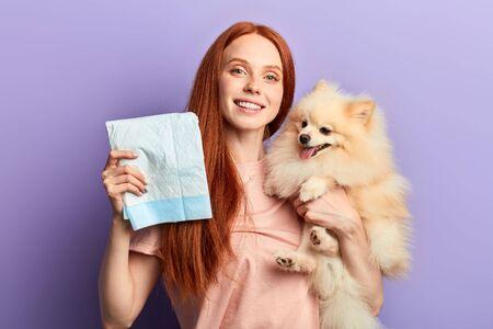 fille assez positive aux cheveux roux contrôlant le processus de pisse de son animal de compagnie. gros plan portrait isolé fond bleu