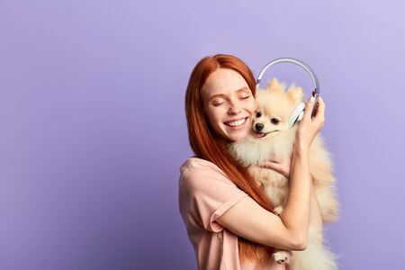 emotional happy pet owner adores her dog, expresses positive feeling . little wonder concept, isolated blue background
