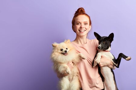 Attractive young smiling ginger woman is embracing her dogs, love and friendship concept. copy space. best friends