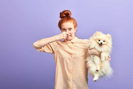 ragazza che tiene un cane randagio puzzolente, l'animale domestico sporco deve essere lavato, cattivo odore dalla bocca del cane. odore sgradevole dell'animale domestico