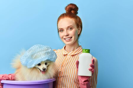 red-haired beautiful smiling girl in striped stylish shirt holding a treatment from fleas while standing over blue background, studio shot.best helper for pet lovers