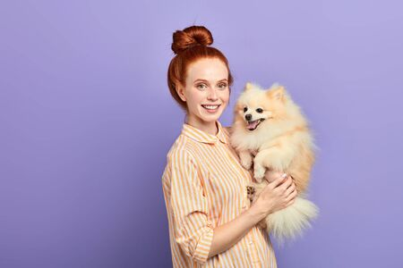 good looking girl in stylish shirt lifting her pet and looking at the camera. close up portrait, isolated blue background, studio shot