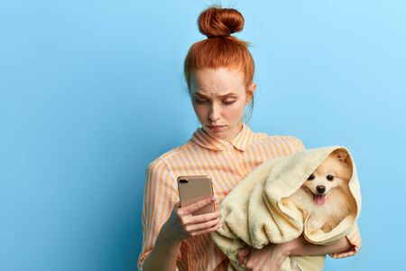 unhappy sad red-haired woman holding a towel with a dog and making a phone call, girl waiting for a vet, as her dog is ill. isolated blue background, studio shot.depression