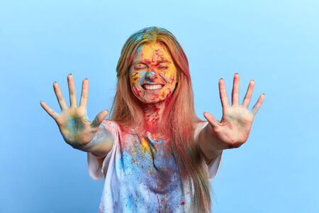 positive smiling girl with closed eyes showing her dirty palms, looking forward holi festival. isolated blue background, studio shot