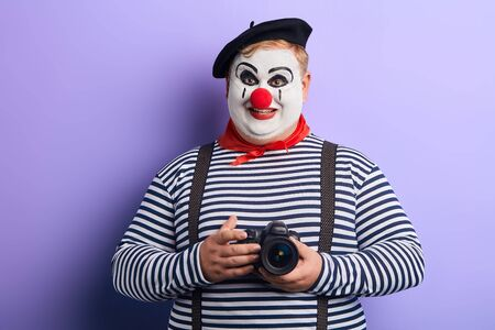 positive awesome plump mime with painted white face and clown nose wearing suspenders and red kerchief going to take a photo, isolated blue background, studio shot.