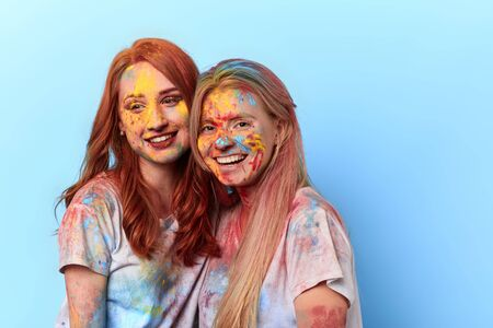 beautiful charming girls have attended festival of colours. close up portrait. isolated blue background. summer tradition and custom