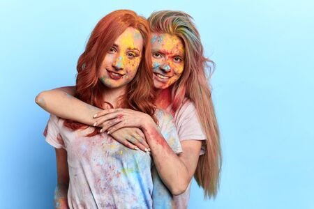 the spirit of colour festival. girls filling their day with colors of joy, prosperity, happiness, peace. isolated blue backround, studio shot . copy space. Reklamní fotografie