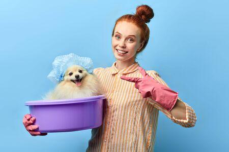 happy positive girl indicating at her pet after water procedures. close up portrait, isolated blue background. studio shot. Reklamní fotografie