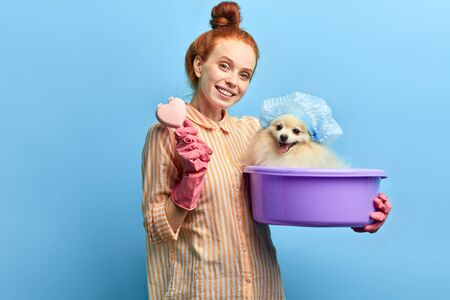 awesome positive girl holding a basin with a dog and hairbrush and looking at the camera, isolated over blue background, studio shot. pets care