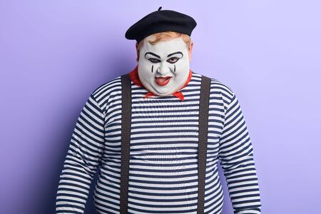 talented clown putting tongue out, trying to make children laughing, happy. close up portrait, studio shot. hungry fat clown licking his lips