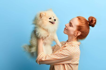 Cheerful beautiful young woman lifting dog up. close up side view photo. warm. tender feeling and emotion . close up portrait, studio shot.girl has received a present on her birthday, gift concept. Banco de Imagens