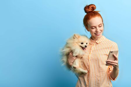 cheerful overjoyed girl and her favourite pet taking a selfie, close up portrait, isolated blue background, studio shot. copy space.lifestyle, free time, spare time. Reklamní fotografie
