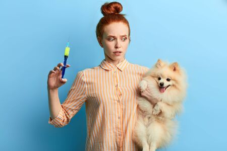 girl being shocked after bad reaction of dog on the injection. girl trying to treat her pet at home, close up portrait. isolated blue background, studio shot. Reklamní fotografie