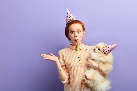 emotional girl with bugged eyes gets pleasure from anniversary of her pet. close up portrait, isolated blue background, studio shot Stock Photo