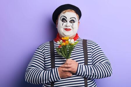 funny smiling mime holding flowers and looking at the camera isolated on blue background. close up portrait. studio shot.positive feeling and emotion
