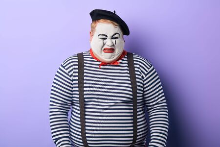 nervous fat artist weeping in the studio with blue wall. emotional unhappy mime isnt satisfied with performance