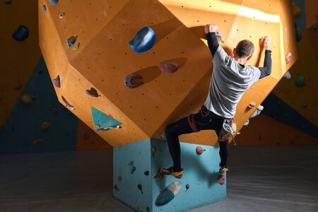 Rear view of powerful physically handicapped man without forearm, trains at bouldering sport center, choosed complicated route, overcomes difficulties, optimistic and strong-willed person. Imagens