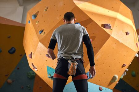 Low angle back view of physically impaired sportsman staring thoughtfully at artificial climbing wall, wearing black sportswear and gray t-shirt, belay system and chalk bag on his waist.