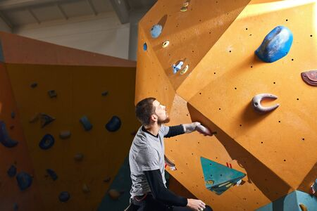 Young motivated rock-climber trains hard in climbing gym club, gets ready to bouldering competition among people with physical disabilities. Motivation and sport concept.