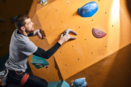 Young ambitious physically challenged man training at bouldering gym, climbing on artificial colourful rock wall, wearing harness and chalk bag, has athletic strong body.