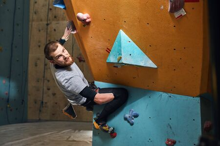 Young handsome physically challenged boulderer with beard hanging at colourful climbing wall, just finished his active training, looking at camera with cheerful smile, feels glad and happy. Imagens