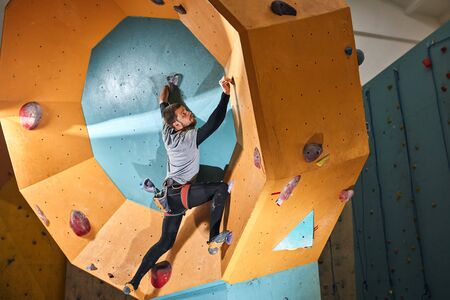 Physically challenged young sportsman moving up at round-shape rock wall, trains every day to improve his climbing skills, wants to take part in upcoming bouldering competition.