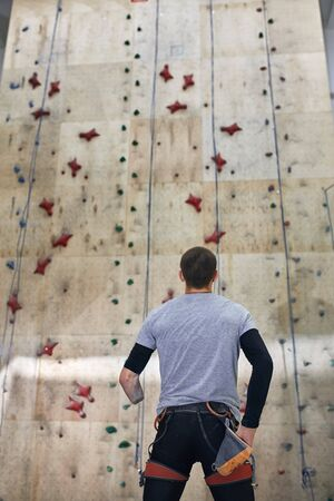 Back view of strong athletic climber with physical disability, standing in front of high wooden rock wall, ready to start climbing training, well-equipped. Half-length shot, low angle view.