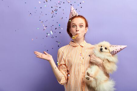 attractive girl and her pet with party hats on their heads spending great magic time. close up portrait, isolated blue background, studio shot Stock Photo