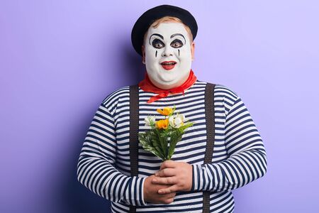 friendly kind mime congratulating all women with Mothers day. holiday concept.isolated blue background, studio shot. lifestyle Foto de archivo