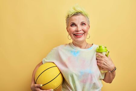 glamour kind of sport. gorgeous granny playing games with her grandsons, isolated yellow background, studio shot. Imagens