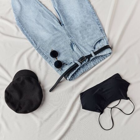 blak top, cap, jeans with belt lying on the white sheet. presentation of comfortable clothing Stok Fotoğraf