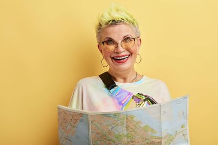 Happy funny positive woman holding a map - isolated over a yellow background. close up portrait. happiness concept