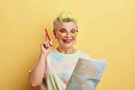 glamour cheerful female tourist in glasses holding paper map,red pencil isolated on yellow background. lifestyle, free time, interest, spare time 写真素材 - 128817583