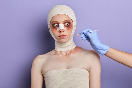 beauty and cosmetic surgery concept . emotional woman looking at beautician hands with syringe. isolated blue background, studio shot Banco de Imagens