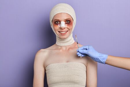cheerful smiling woman is happy to get treatment in best cosmetic clinic. close up portrait, isolated blue background, studio shot