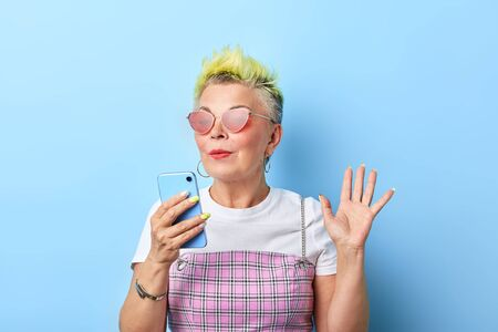 stylish old woman with raised hand greeting her best friend while making a phone call. close up portrait, isolated blue background, studio shot.