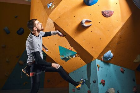 Male physically challenged boulderer standing and staring thoughtfully at difficult climbing wall, planning how to reach the top, dressed in black sportswear, gray t-shirt and special climbing shoes.