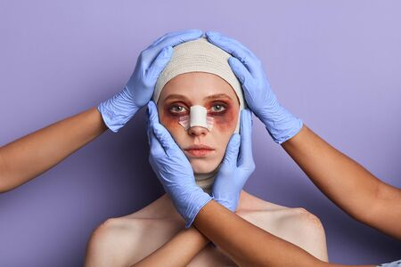 plastic surgeon treating facial injuries. close up portrait, isolated blue background, reconstruction of face after insidents, treating defects