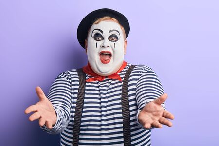 positive mime entertaining kids during the party.close up portrait, isolated blue background, studio shot.happiness, joy