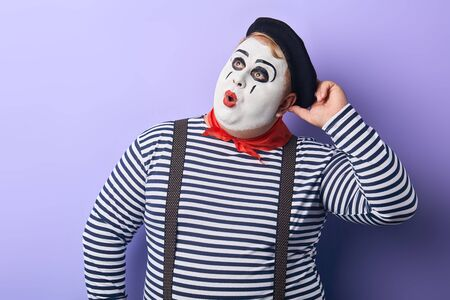 pensive mime touching his cap and looking up isolated on blue. close up portrait, isolated blue background, studio shot.facial expression.