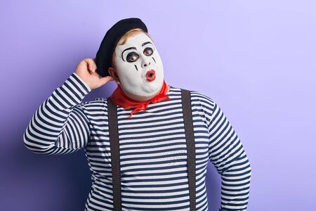 thoughtful clown in striped sweater, suspender and hat with hand on his head solving problem. close up portrait, isolated blue background, studio shot