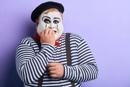 frightened emotional fat clown in striped sweater, suspenders and beret biting his nails, isolated blue background, copy space. place for text, advert.
