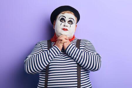 portrait of fat mime man pretending praying on blue background. copy space. joy, fun, comedy.