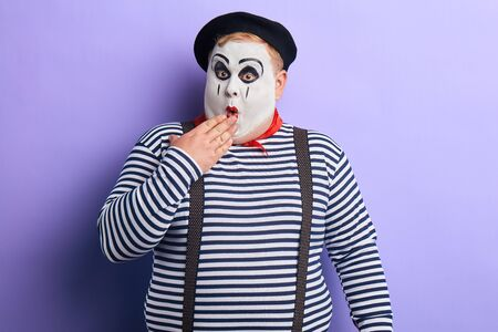 Shocked funny mime artist standing in disbelief closing his mouth with a palm isolated on blue background. close up portrait. studio shot.copy space Stock Photo